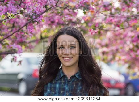 Portrait Of Young Beautiful Brunette Woman Standing In Front Of Tree With Pink Flowers In Springtime