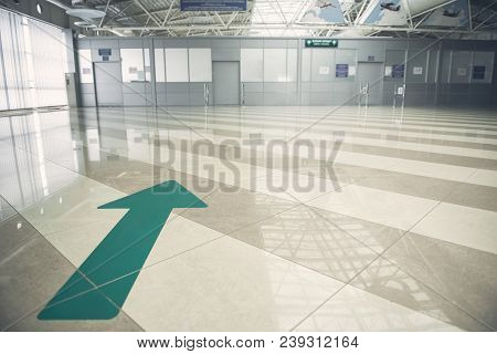 Big Green Arrow Pointing At White Closed Door While Locating On Striped Floor In Airport Hall