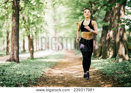 Running Woman On Park. Female Runner Jogging During Outdoor Workout In A Park.