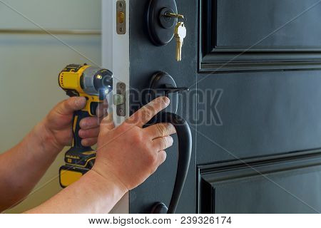 Closeup Of A Professional Locksmith Installing A New Lock On A House Exterior Door With The Inside I
