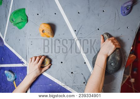 Close-up Of Artificial Hooks And Hands Of Climber On Climbing Wall