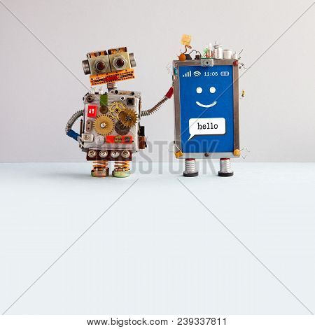 Robot And Smiley Mobile Cellular Gadget. Robotic Toy Characters On Beige Gray Background. Creative D