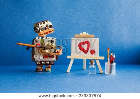 Robot Artist With Brush In Hand Looks At The Red Heart And A Blot Painted In Watercolor On White Pap