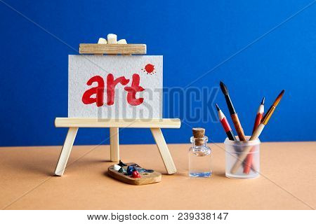 Word Art With Red Blot On Watercolor Textured Paper. Beautiful Wooden Easel In Art Class Studio Inte