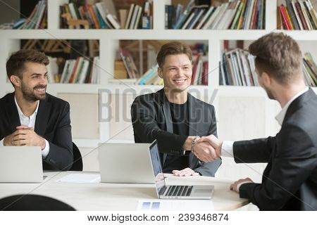 Male Ceo Welcoming New Colleague By Handshake Sitting At Conference Table In Modern Office Brainstor