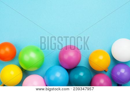 Colorful Balloons On Blue Table Top View. Festive Birthday Background. Flat Lay Style.
