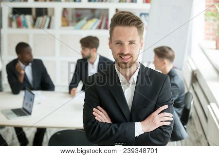 Portrait Of Smiling Caucasian Worker Looking At Camera Standing At Foreground, Colleagues Negotiatin