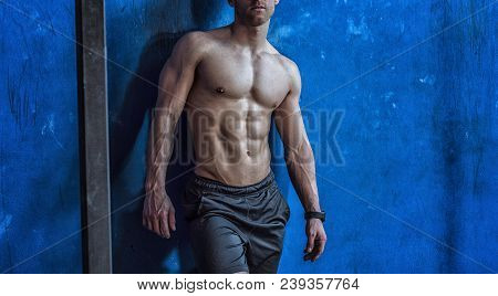 Attractive And Muscular Shirtless Young Man Leaning Against Wall In Gym, To Rest Or Relax After Work
