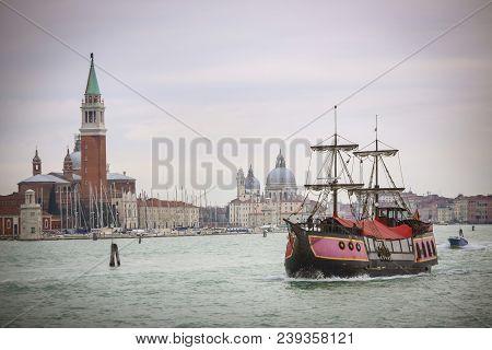 Galley Ship Sailing In Water Channel With The Church Of San Giorgio Maggiore And Santa Maria Della S