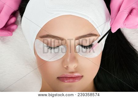 Young Model With Pretty Face Lying During Lashes Enlarging. Professional Is Making Long Lashes For A