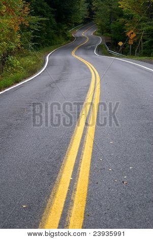 a long curvy winding road with double yellow lines poster