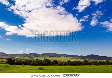Beautiful Summer Sky Over The Mountainous Area. Lovely Countryside With Forested Hills And Fields