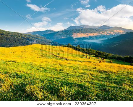 Beautiful Rural Scenery In Mountains At Sunrise. Haystacks On The Field Behind The Fence. Outdated A