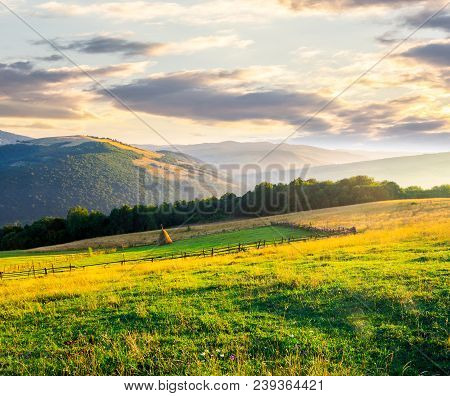 Beautiful Rural Scenery In Mountains At Sunrise. Haystack On The Field Behind The Fence. Outdated Ag