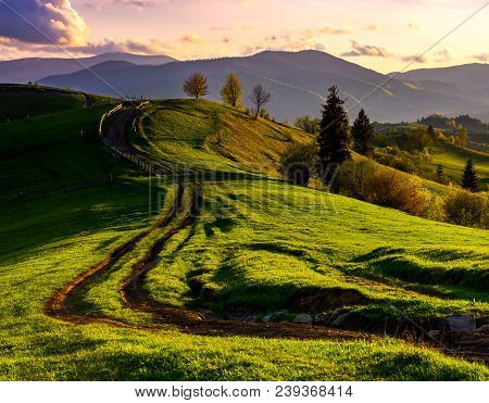 Road Through Green Hills At Sunset. Beautiful Springtime Rural Landscape In Mountains Under The Sky