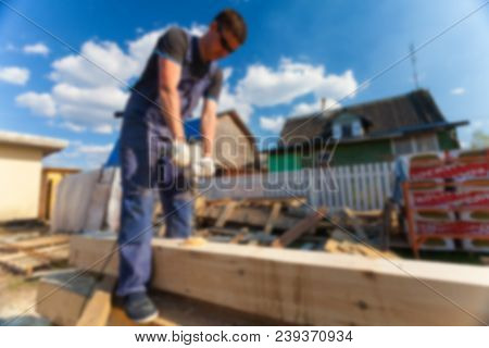 Blurred Carpenter -worker- With Big Professional Tool -electric Drill- Is Drilling Wood Beam During