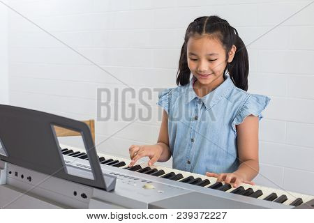 Asina Children Young Girl Playing Piano In Music Room At School .