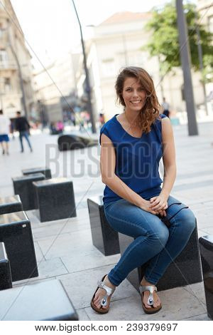 Attractive young woman sitting outdoors in the city, smiling happy.