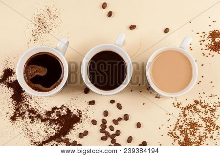 Three Cups Of Coffe With Ground And Instant Coffee And Roasted Beans From Above.