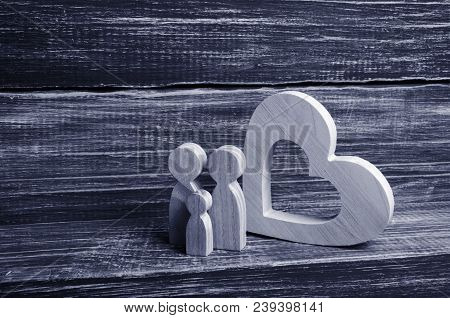 A Young Family With A Child Is Standing Near A Wooden Heart. Love And Loyalty, A Strong Young Family