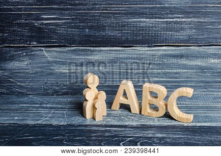 The Pupil And Pupils Stand At The Big Letters Abc Of The English Alphabet. Parent And Children. The