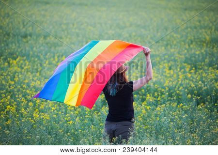 Young woman holding gay rainbow flag in the field