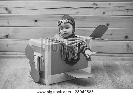Small Child In Pilot Costume Dreaming Of Piloting The Plane, Playing With Toy