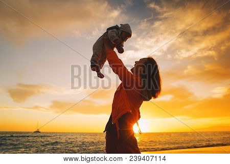 Mother And Baby Silhouettes At Sunset On The Sea Beach