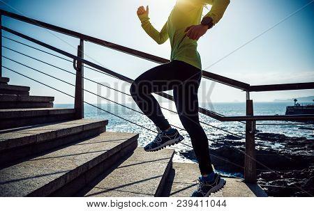 sporty female jogger running upstairs on seaside during sunrise poster