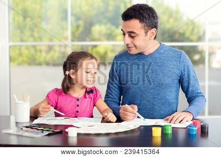 Little Girl And Father Are Drawing Pictures Together