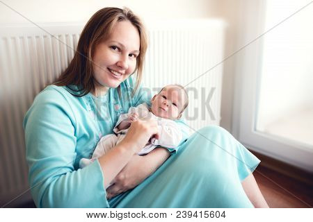 Mother And Her Newborn Baby At Home