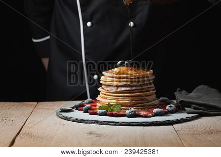 Front View Of Stack Of Homemade Plain Pancakes With Strawberries, Blueberries And Maple Syrup Served