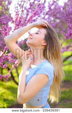 Charming Woman Resting In Park Near Trees In Blossom. Concept Of Sring Inspiration.