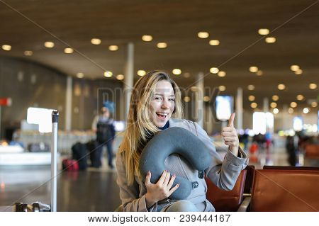 European Woman Sitting With Neck Pillow And Valise In Airport Waiting Room, Showing Thumbs Up. Conce