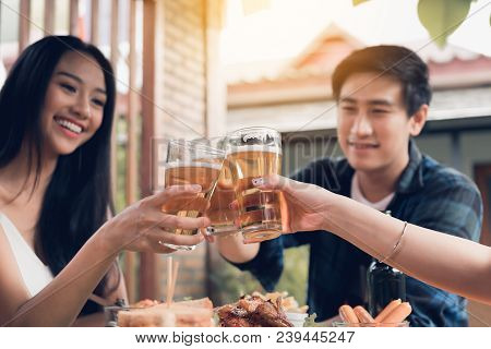 Close Up Of Beer Glass With Asian People Drinking Beer In Restaurant.