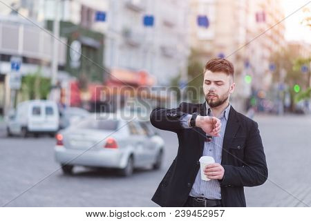 Portrait Of A Handsome Business Man Standing With A Cup Of Coffee In His Hands, Looking At The Wrist
