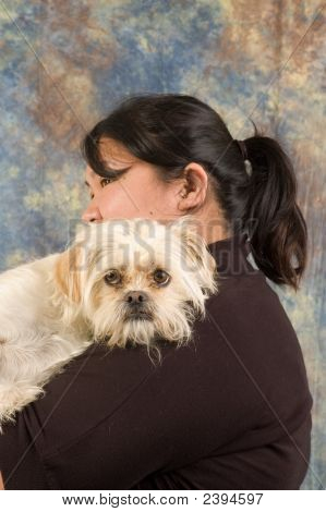 Asian woman holding pet dog in arms poster