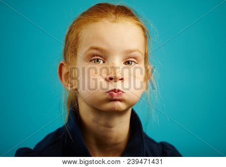 Portrait Of Seven Year Old Girl With Inflated Cheeks, Has Red Hair And Freckles, Close-up Shot On Bl