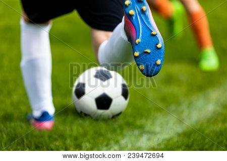 Soccer Kick. Footballer Kicking Ball On Grass Pitch. Football Soccer Player Hits A Ball. Soccer Boot