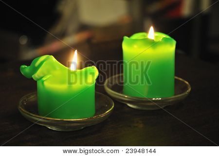 Molten green candle against a dark background