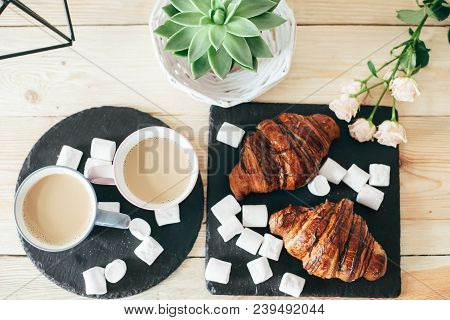 Two Cups Of Coffee With Milk, Two Croissants At Black Plate On Wooden Table. French Breakfast For Tw