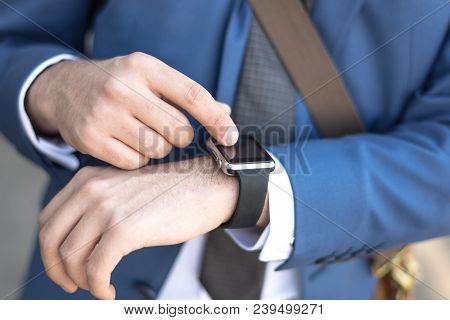 Person Using Smart Watch And A Smartphone Walking On The Park In A Sunday. Young Man Making Gestures