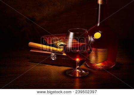 Bottle of cognac Courvoisier ( Le Voyage de Napoleon),  glass with cognac, wooden box with cigar stand on a table on a wooden background.