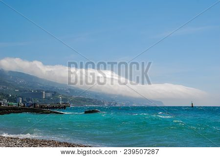 The Shore Of The Blue Sea, On The Shore Are Mountains, Covered With Green Trees. Over The Mountains