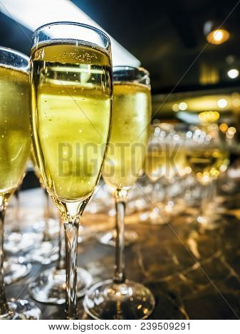 Ready-to-serve glasses of white wine in the foreground. All queued to serve guests in a home party function. poster