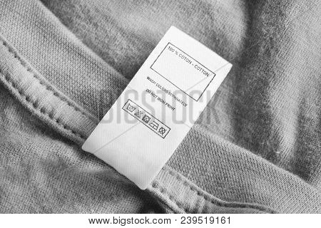 Care And Composition Clothes Label On Grey Cotton Background
