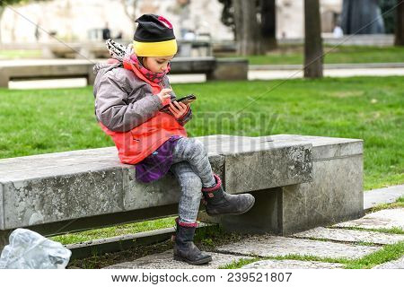 Little Girl Child Using A Mobile Phone In Public Park.