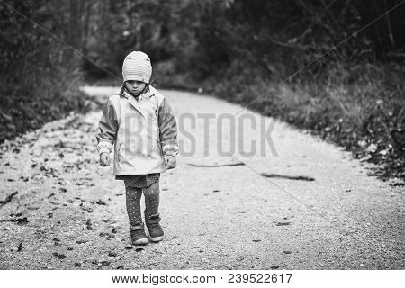 Young Sad Girl Child Is Walking Alone On Country Road. Abandoned Sad Little Girl Is Walking In Natur
