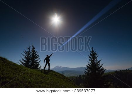 Man Standing On A Mountain Hill And Points By Flashlight To The Night Starry Sky.
