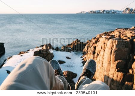 Young Brave Traveler Resting On Rock In Front Of Snowy Cliff And Blue Ocean And Look On Feet. Pov Vi